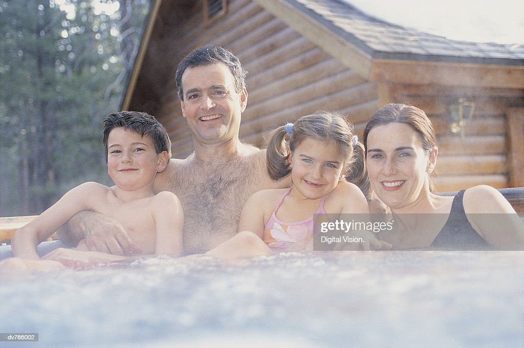 Portrait of a Family of Four Relaxing in a Hot Tub in Front of a Snow Covered Chalet : Foto de stock