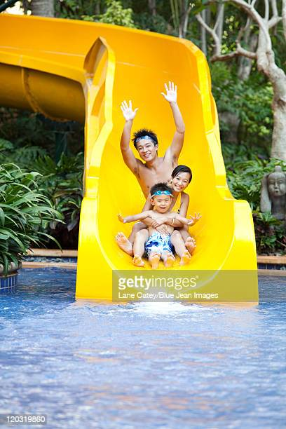 Portrait of a family of three on a water slide