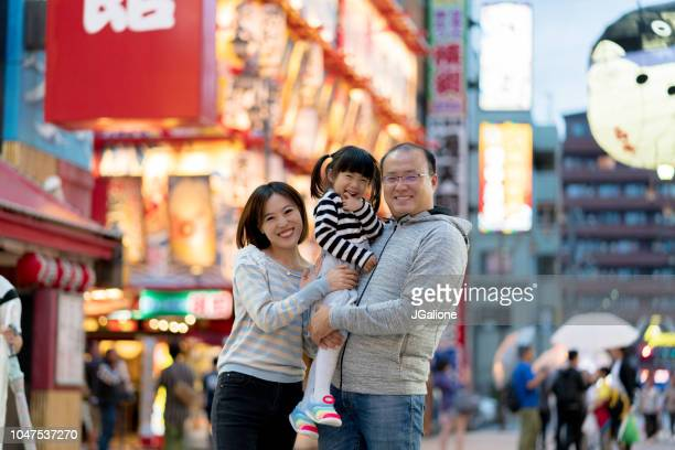 portrait of a family of tourists exploring a japanese shopping district - chinese ethnicity stock pictures, royalty-free photos & images