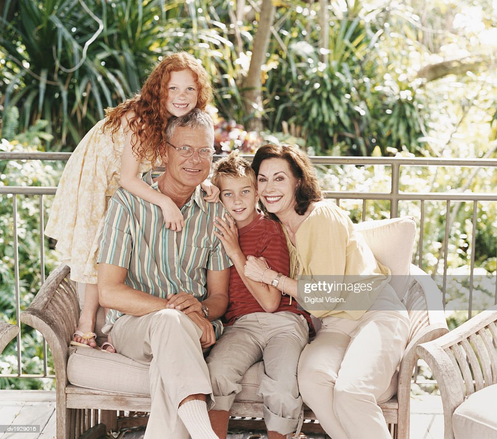 Portrait of a Family of Two Children Sitting on a Sofa on Their Porch : Stock Photo