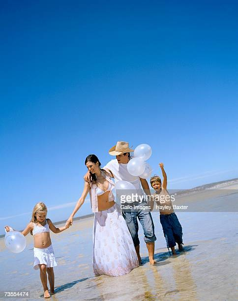 portrait of a family on the beach - bikini top stock pictures, royalty-free photos & images