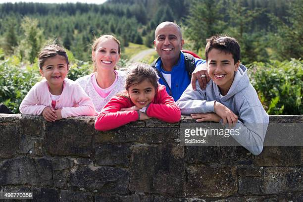 Portrait of a Family outdoors surrounded by the countryside.