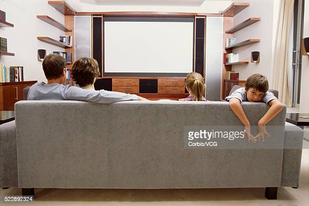 Portrait of a family relaxing on the couch in front of a large screen TV