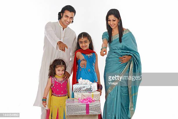 Portrait of a family showing diwali gifts
