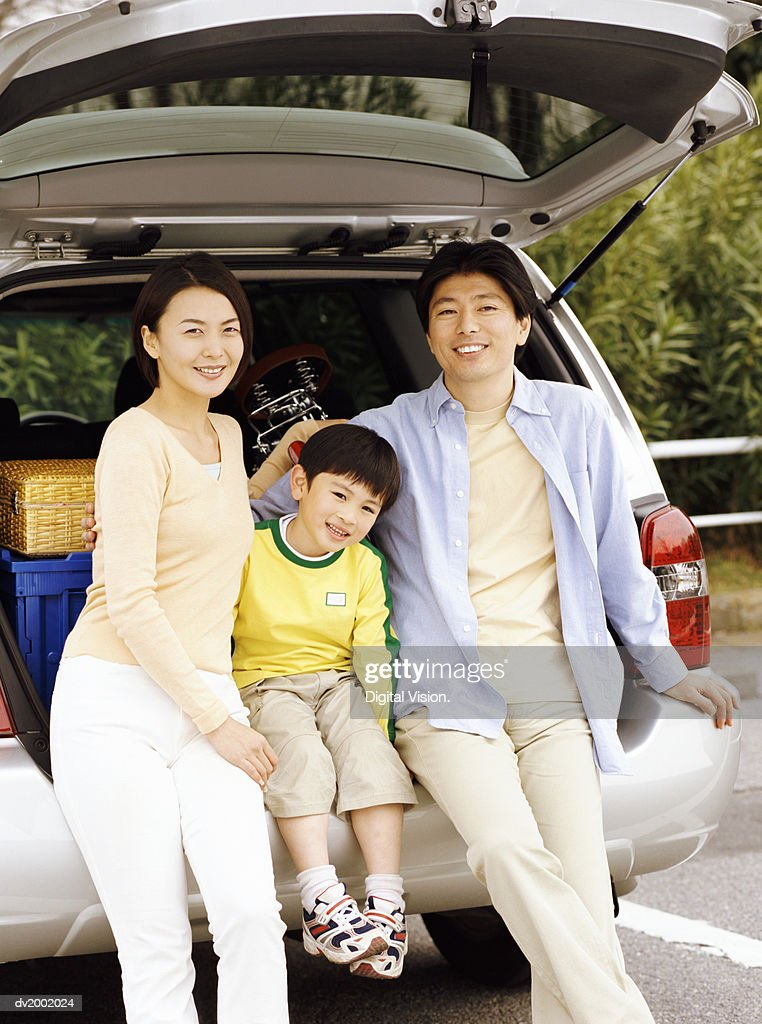Portrait of a Family Sitting Against the Back of a Car : Stock Photo
