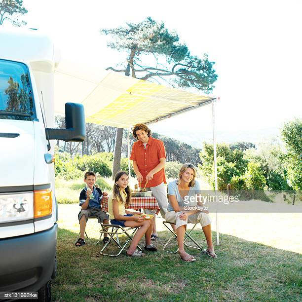 portrait of a family sitting at a picnic by their caravan