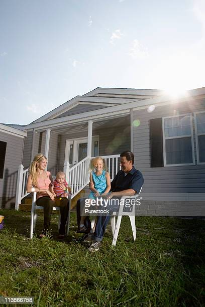 Portrait of a family sitting in front of a trailer home