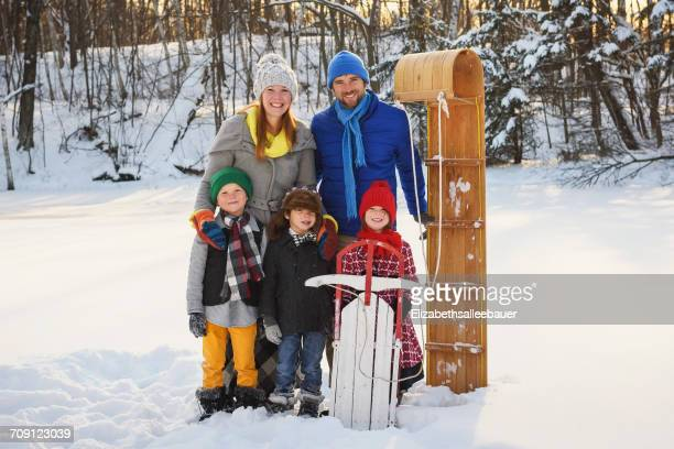 Portrait of a family standing in snow with a sledge