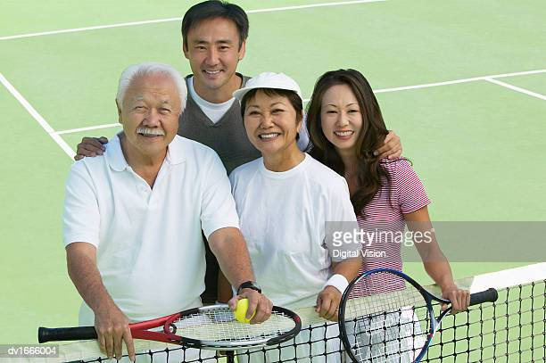 Portrait of a Family Standing Together on a Tennis Court
