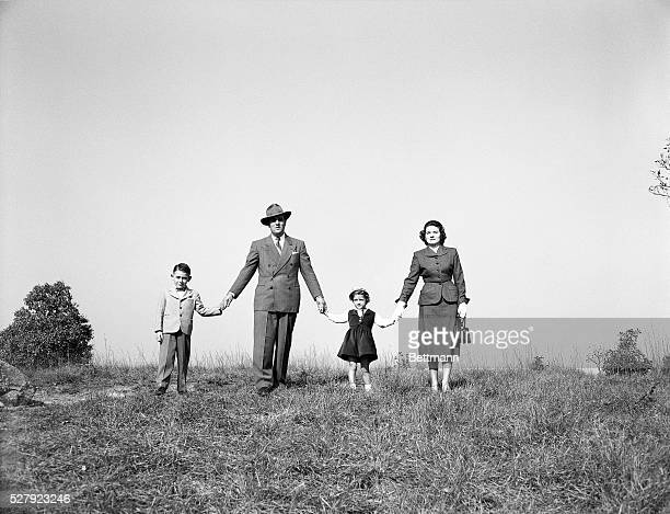 Portrait of a family walking in a grassy field holding hands Undated photograph circa 1950's