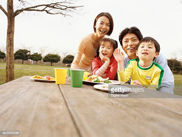 Portrait of a Family With a Young Son and Daughter Sitting at a Picnic Table
