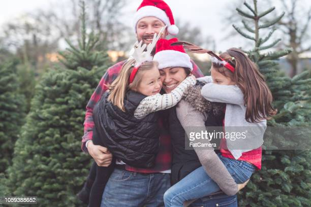 portrait of a family with two kids at the christmas tree farm - christmas photos stock photos and pictures