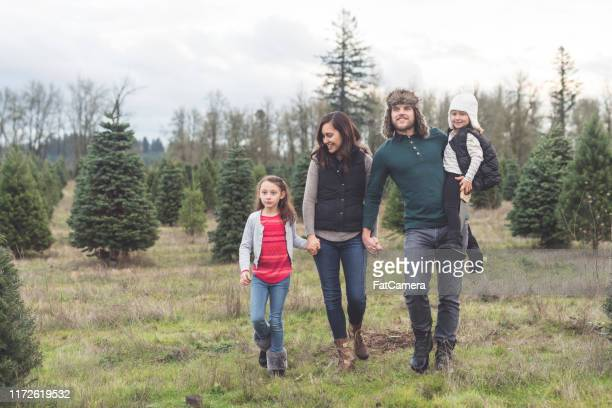 portrait of a family with two kids at the christmas tree farm - tree farm stock pictures, royalty-free photos & images
