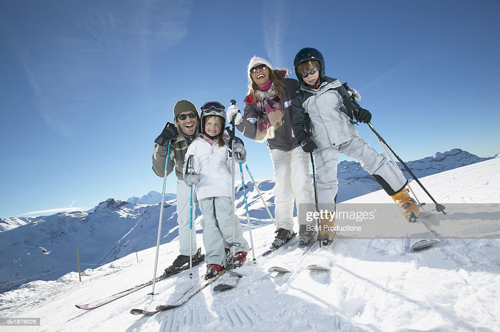 Portrait of a Family With Two Young Children in Skiwear Standing on a Ski Slope : Stock Photo