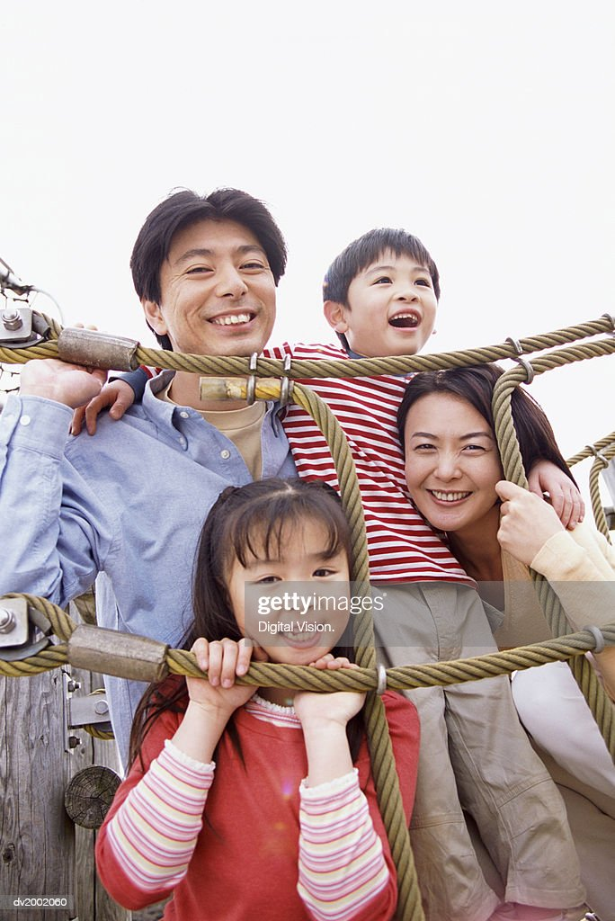 Portrait of a Family With Two Young Children on a Climbing Frame : Stock Photo