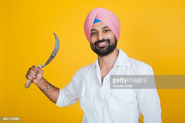 Portrait of a farmer holding a sickle