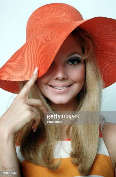 1965 A portrait of a fashionable young woman wearing a large rimmed red straw hat whilst smiling at the camera