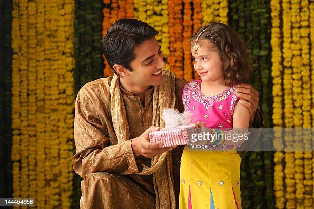 portrait of a father and daughter holding a gift box - bangle stock pictures, royalty-free photos & images