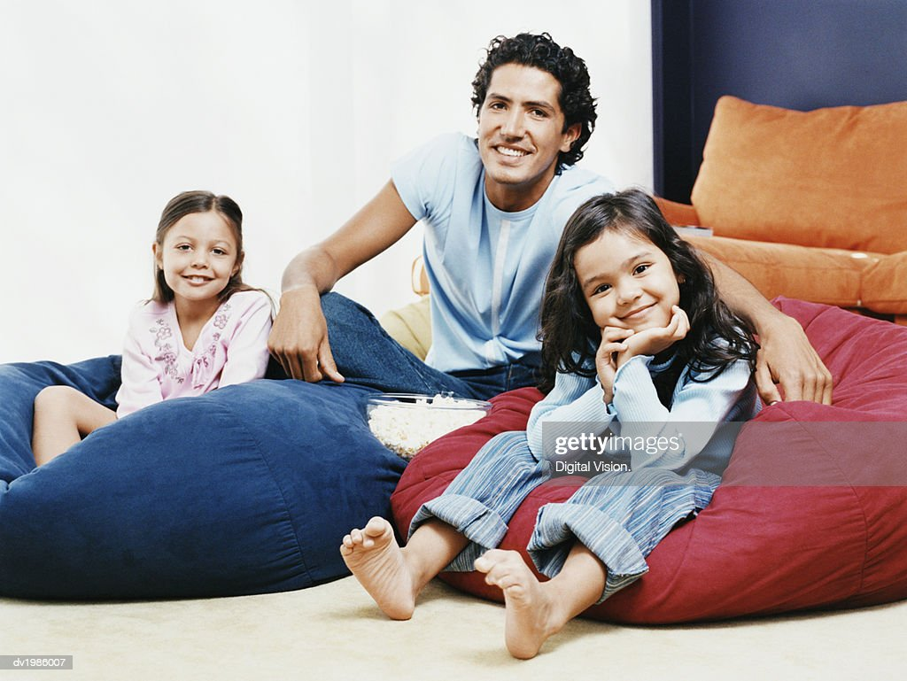 Portrait of a Father and His Daughters Sitting on Beanbags : Stock Photo