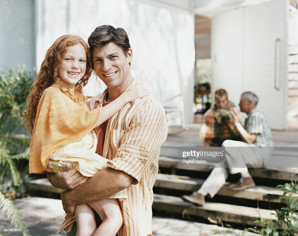 Portrait of a Father and His Young Daughter Outside Their Home : Stock Photo