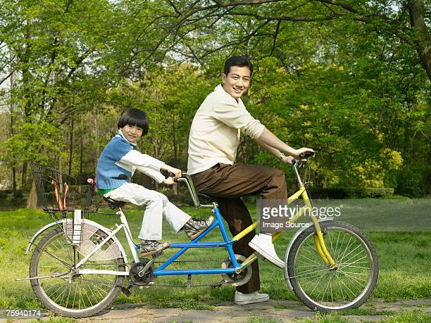 portrait of a father and son on a tandem bike - tandem bicycle stock pictures, royalty-free photos & images