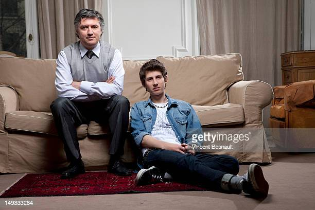Portrait of a father and teenage son at home