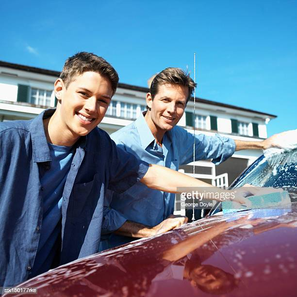 portrait of a father and teenage son (18-20) washing the car - red tube top stock photos and pictures