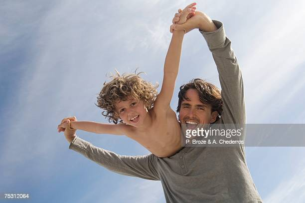 Portrait of a father carrying his son on his back, outdoors