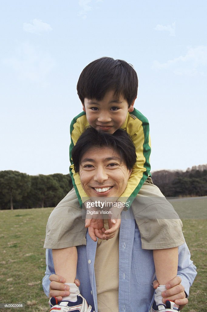 Portrait of a Father Carrying His Young Son on His Shoulders : Stock Photo