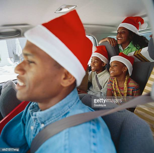 portrait of a father driving with his children (8-10) in a car wearing christmas caps - pere noel voiture photos et images de collection