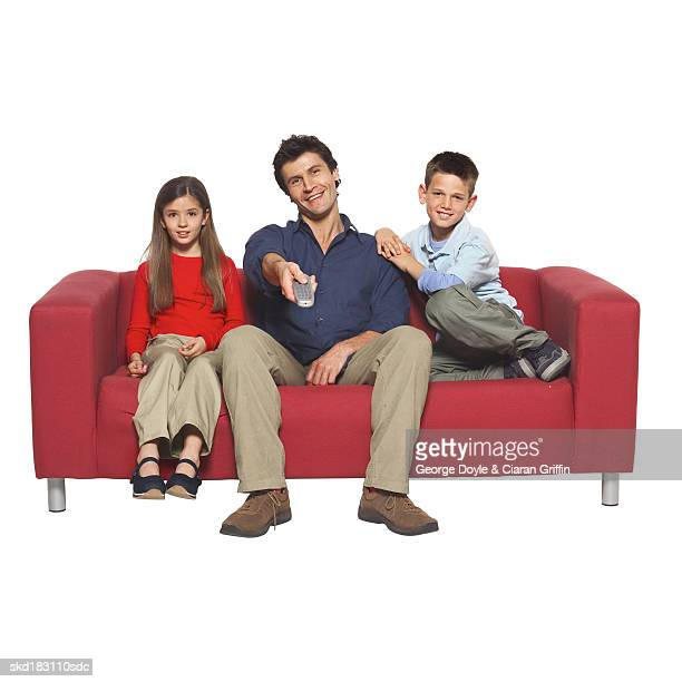 Portrait of a father holding remote control and two children (10-12) sitting on couch