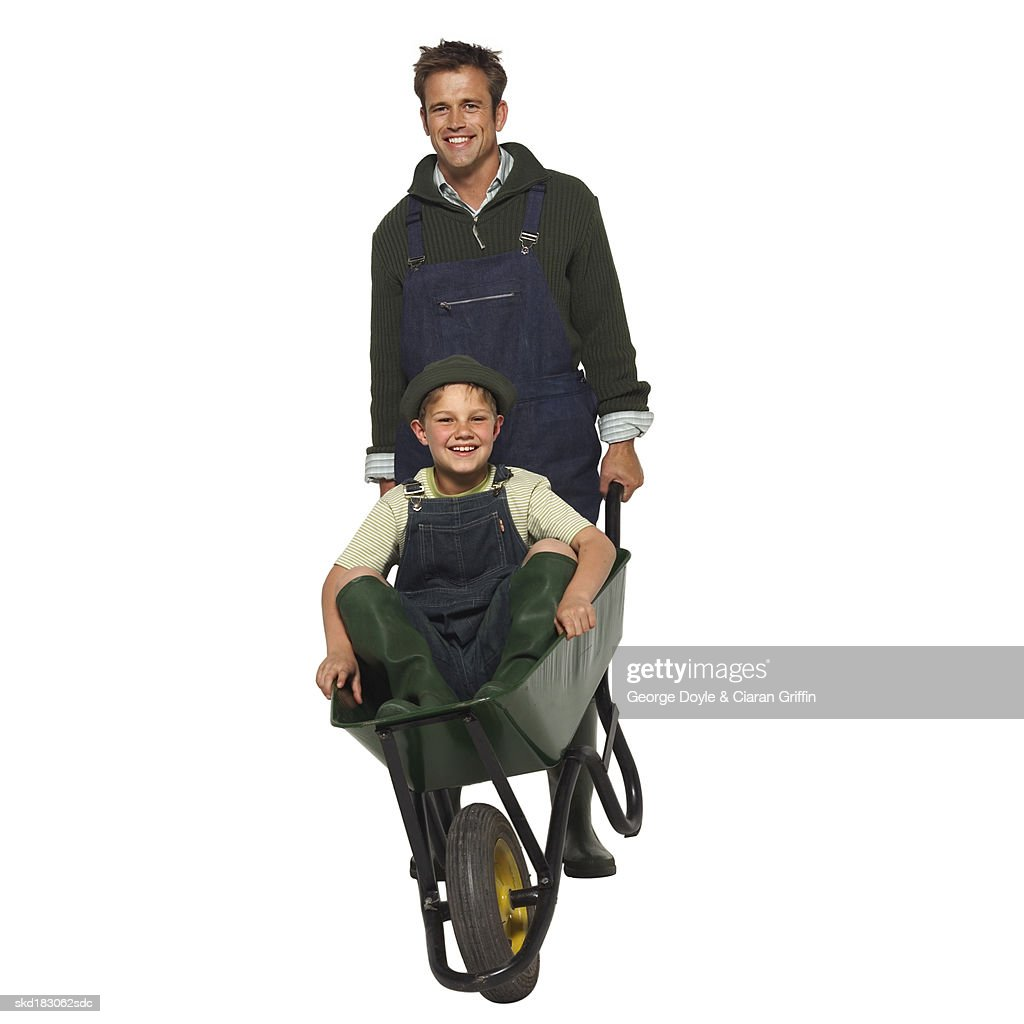 Portrait Of A Father Pushing His Son In A Wheelbarrow Stock