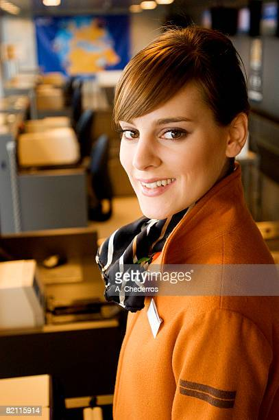 Portrait of a female airline check-in attendant smiling at an airport check-in counter
