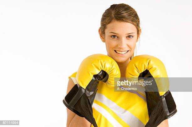 Portrait of a female boxer wearing boxing gloves and smiling