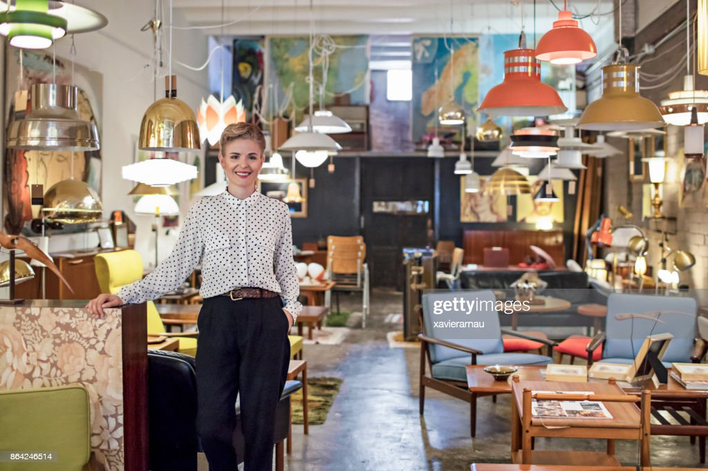 Portrait of a female business owner standing in her furniture store : Foto de stock
