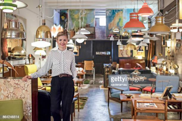 portrait of a female business owner standing in her furniture store - antique stock pictures, royalty-free photos & images