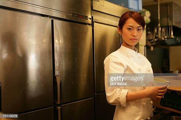 Portrait of a female chef holding a tea cup