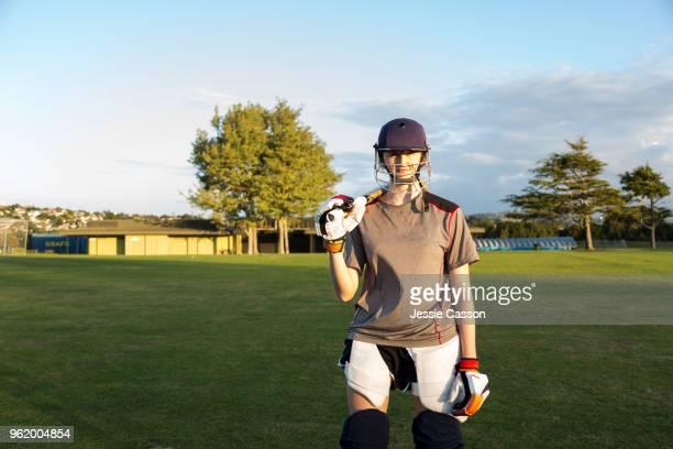 portrait of a female cricketer wearing protective helmet - cricket spieler stock-fotos und bilder