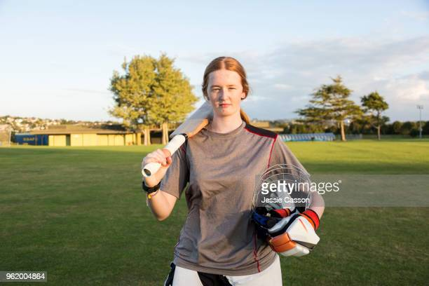 portrait of a female cricketer with bat on sports field - cricket player stock pictures, royalty-free photos & images
