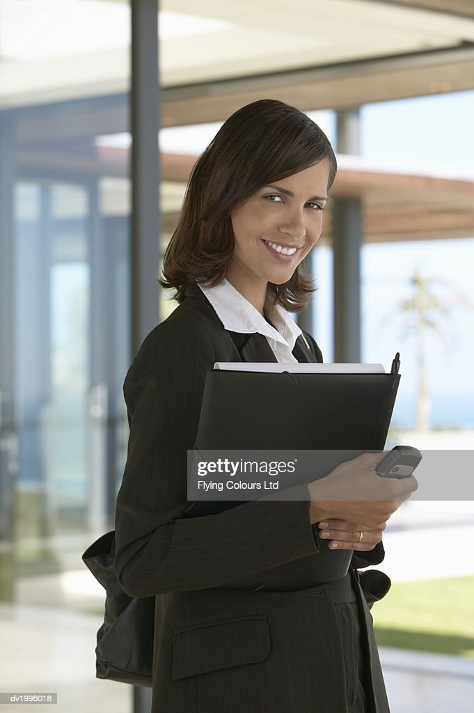 Portrait of a Female Estate Agents Standing Holding a Folder and Mobile Phone : Stock Photo