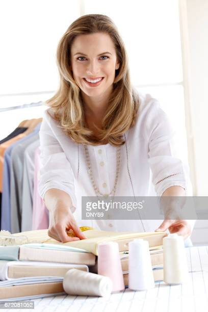 Portrait Of A Female Fashion Designer As She Measures A Piece Of Fabric