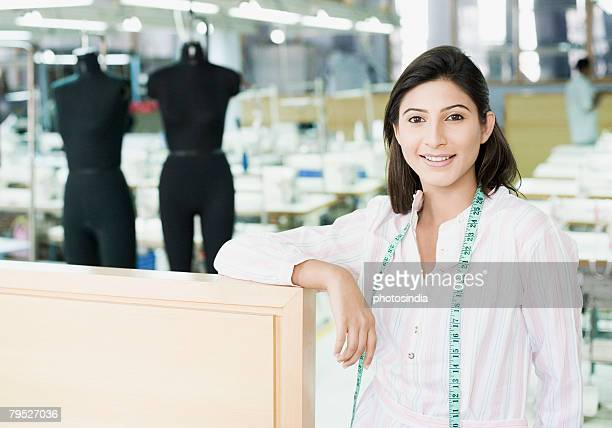 Portrait of a female fashion designer standing in a textile industry and smiling