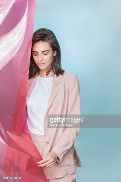 portrait of a female fashion model posing with pink fabric and looking down - chaqueta rosa fotografías e imágenes de stock