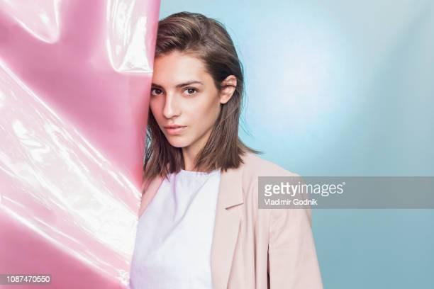 portrait of a female fashion model posing with pink fabric - chaqueta rosa fotografías e imágenes de stock