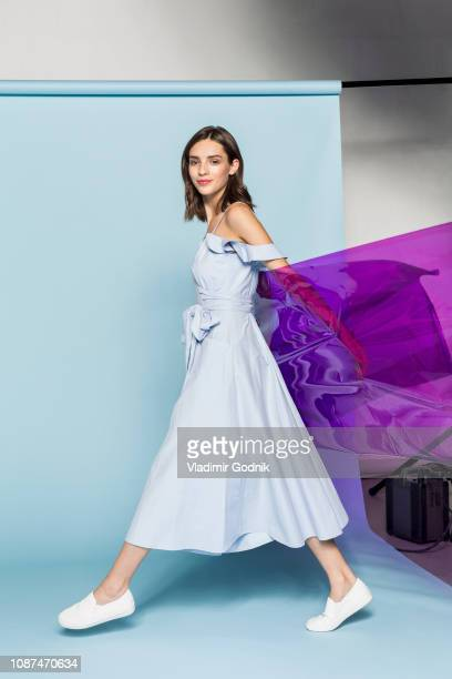 portrait of a female fashion model posing with purple plastic sheet against blue background - dress stock pictures, royalty-free photos & images