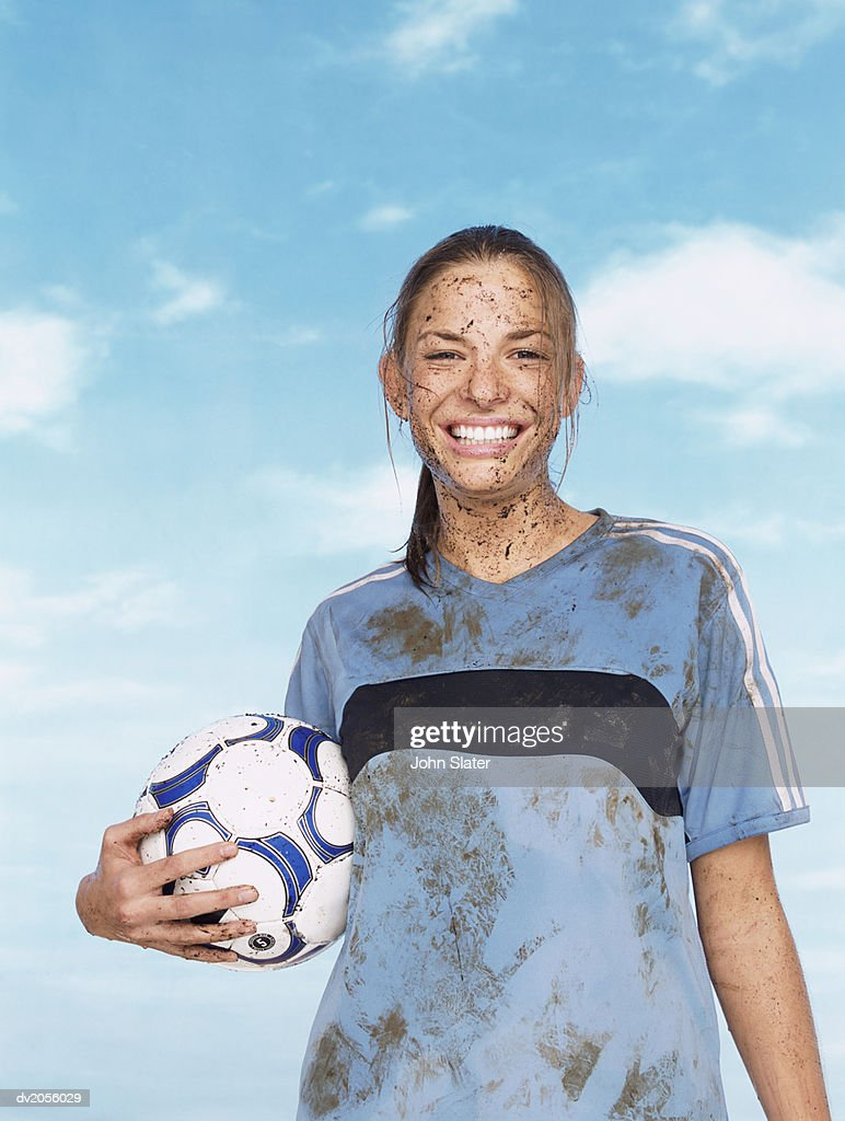 Portrait of a Female Footballer Covered in Mud and Holding a Football : Stock Photo