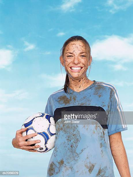 Portrait of a Female Footballer Covered in Mud and Holding a Football