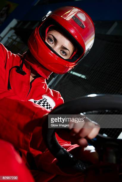 portrait of a female go-cart racer sitting in a sports car - sportschutzhelm stock-fotos und bilder