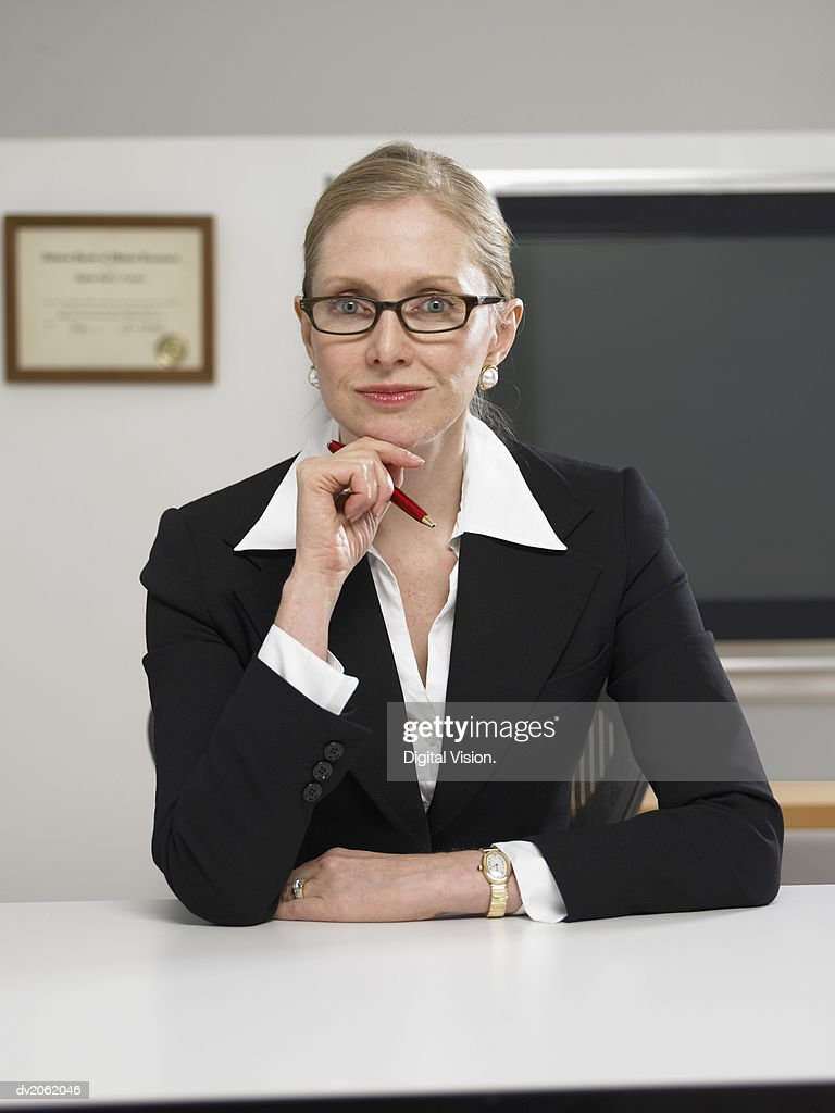 Portrait of a Female GP Sitting at Her Desk in Her Clinic : Stock Photo