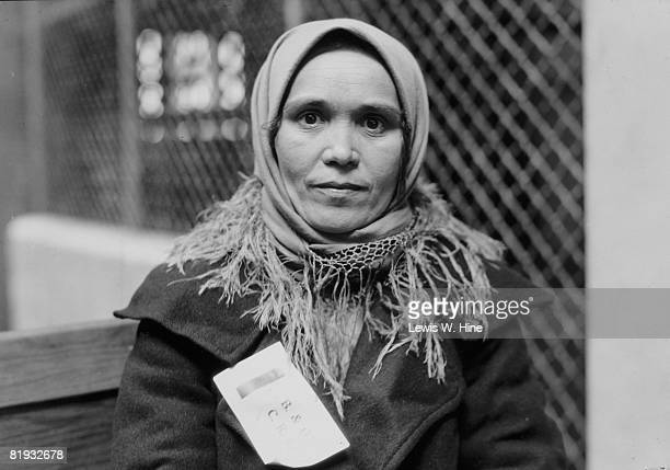 Portrait of a female immigrant from an unknown country passing through Ellis Island in New York, She wears a railroad tag bearing the letters B&O New...